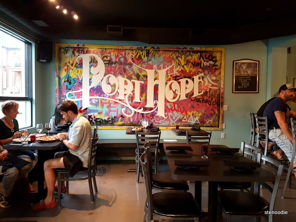 "The inside view of Local90, with a colourful mural that reads ""Port Hope"""