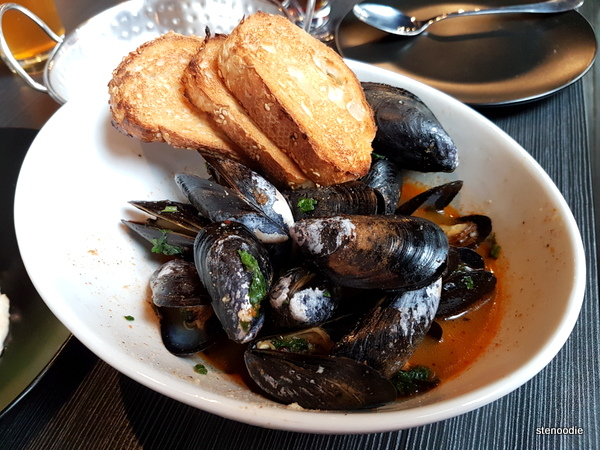 Steamed mussels in white wine, chipotle, garlic and herbs.