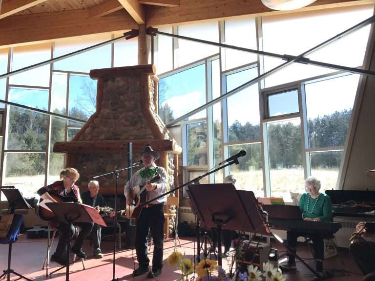 A band plays inside the lodge which boasts a large stone fireplace and full picture windows